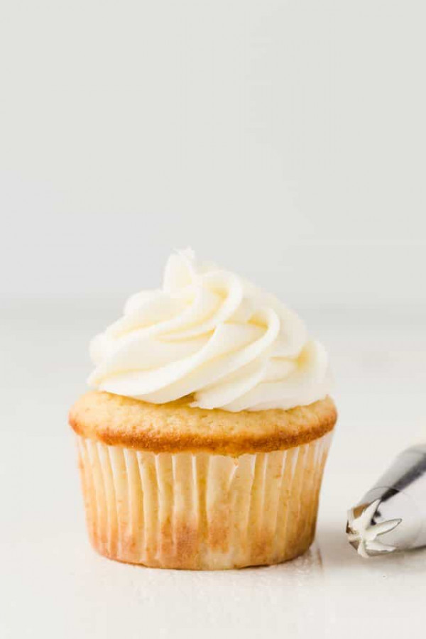 Coconut buttercream frosting swirled on top of a vanilla cupcake.