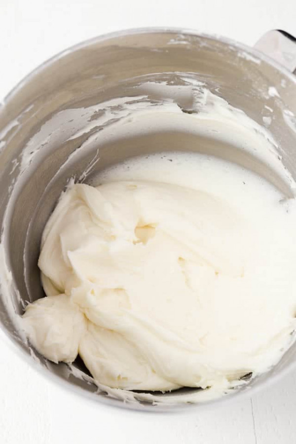 Whipped coconut buttercream frosting in a stainless steel bowl.
