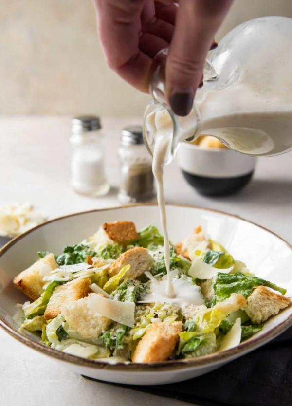 Pouring homemade caesar salad dressing